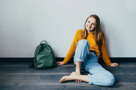 teenage girl looking on cellphone and smiles sitting on wooden floor. Beautiful girl in yellow sweater and blue jeans with backpack thrown nearby. Trendy casual outfit. 스톡 콘텐츠