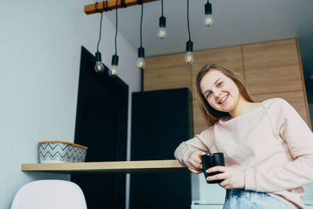 American teenage girl at Home kitchen interior holding Black coffee cup. Woman in pink blouse and blue jeans lean on wooden countertop. Modern interior design and black wire chandelier with light bulb 스톡 콘텐츠