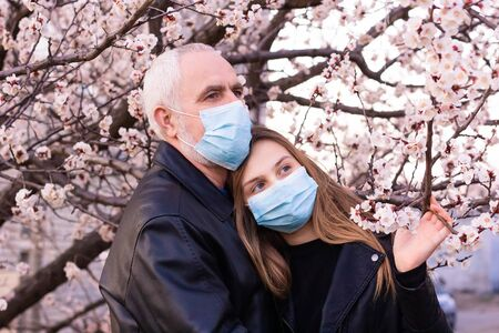 teenage girl and senior man  in face mask, standing in a flowering apricot blossom garden, support during pandemic and worry about  grandfather during world pandemic of coronavirus epidemic.