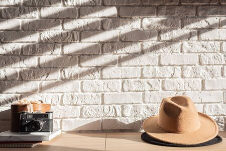 wooden shelf with retro photo camera, books and hat in Sunshine. Stylish interior of living room with white brick wall, brown box, elegant accessories. Minimalistic concept of home decor. Template.