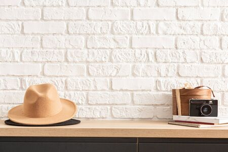 wooden shelf with retro photo camera and hat. Stylish interior of living room with white brick wall, brown box, elegant accessories. Minimalistic concept of home decor. Template.