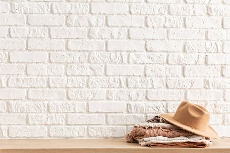 Women's casual outfits and brown trendy hat on wooden table over white brick wall. 스톡 콘텐츠