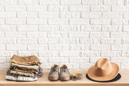 Men's casual outfits on wooden table over white brick wall background with place for text. Shoes, hat, belt and clothes. elegant male accessories. Minimalistic concept of home decor.