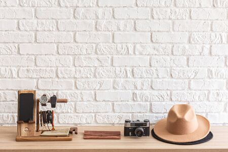 Men's casual accessories on wooden table over white brick wall background with place for text. Cellphone, wristwatch, retro photo camera and brown hat. elegant male accessories.  스톡 콘텐츠
