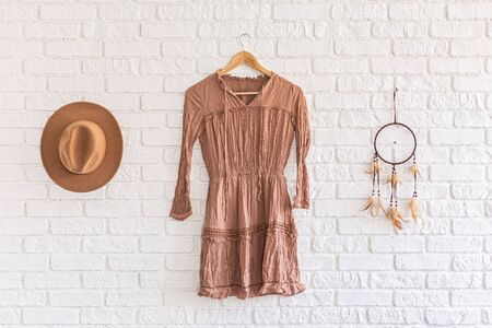 Fashion woman summer dress, hat and dream catcher hanging on white brick wall background. beautiful set clothes hanging on a hanger on a brick wall in a loft studio. Nobody. Showroom