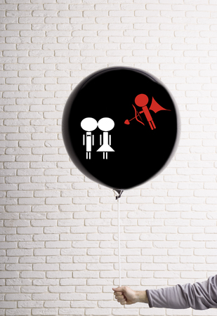 a big black balloon in the hand on which a cupid with a bow and arrow is drawn. valentine's day concept. aims in a pair. against a white brick wall Stock Photo