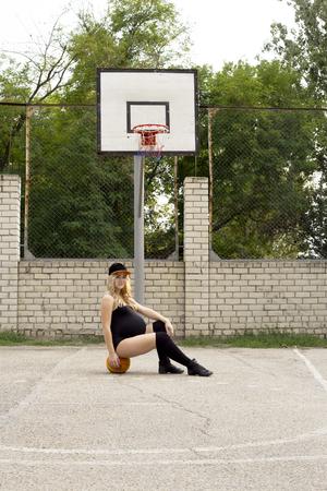 pregnant girl on the basketball court sits on the ball. sport Reklamní fotografie - 119243071