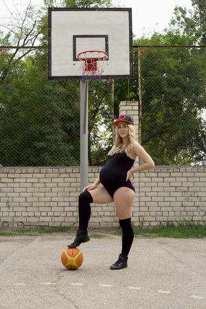 A pregnant girl on the basketball court stands near the ring with her foot on the ball. sport