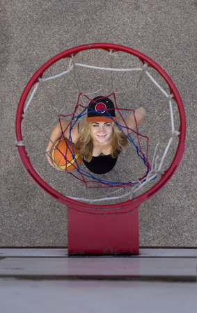 pregnant girl on the basketball court stands under the ring view from the top. sport Stock Photo