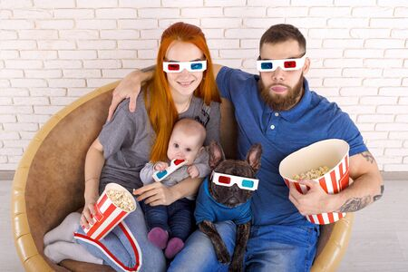 Young family with young children and a dog in 3D glasses. cinema concept. with popcorn in hand. on the sofa against the brick wall. top view Stockfoto