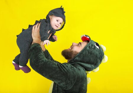 funny dad and daughter in dragon costume. on a yellow background. Dad holds daughter in his arms over his head. happiness