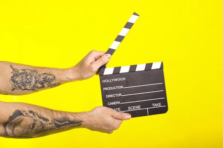 director's clapper. hands with a boardсlapper on a yellow background. cinema concept