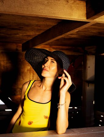 beautiful young brunette girl in a yellow bathing suit and hat
