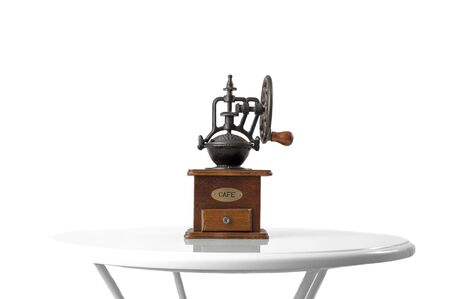 vintage hand coffee grinder. standing on table. isolated on white background