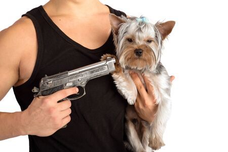 the guy is holding a dog in his arms. threatens her with a gun. isolated on white background Banque d'images