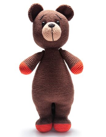 Cute handmade toy. knitted little animal. bear. on a gray background. Crochet stuffed animals.