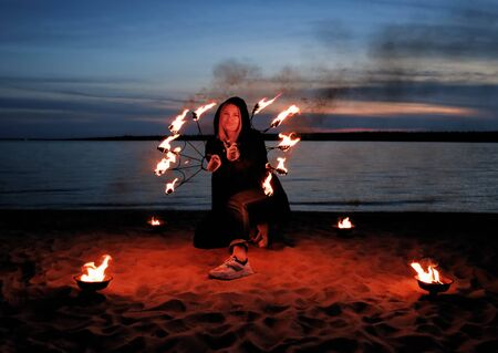 young girl by the sea shows a show with fire. details for working with fire. work with fire in nature.