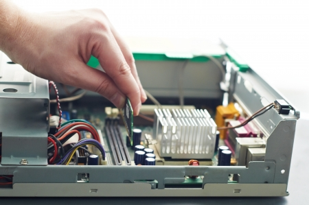 Human hand inserting RAM memory into computer  during repair
