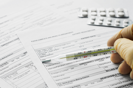 heat register: Thermometer in man hand on patient registration form