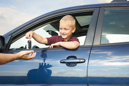 Happy child showing keys from car