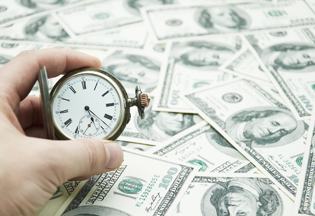 action fund: Hand holding watch on dollar banknotes
