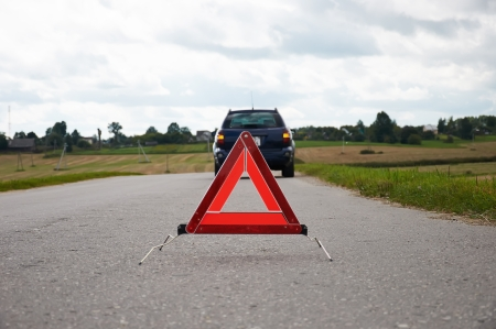 Red warning triangle with a broken down car Standard-Bild