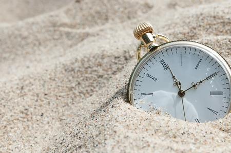 砂に埋もれている懐中時計 写真素材