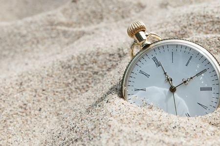 forgotten: Pocket watch buried in sand Stock Photo