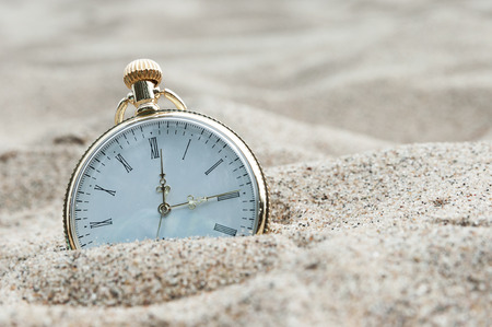 yesterday: Pocket watch buried in sand Stock Photo