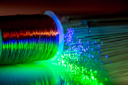 blue and green glowing fiber optic wire against copper wire