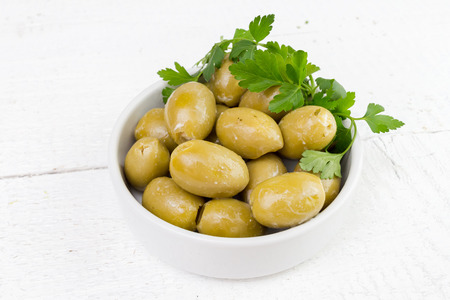 pickled green olives olea europaea mediterranean decorated with parsley in a white bowl on a wooden board