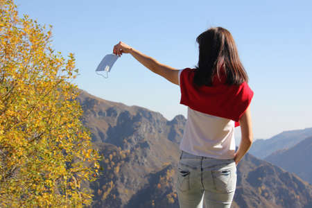 Young woman throwing away medical single-use face mask in nature. Coronavirus free, removing protective, environmental pollution concepts.