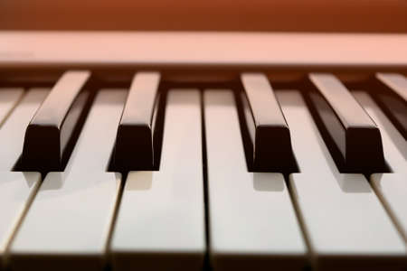 Close up detail of electronic musical keyboard synthesizer in orange light.
