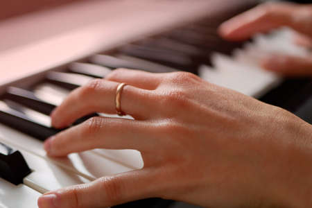 Woman musician hands playing piano keyboard, MIDI synthesizer, home music learning. Zdjęcie Seryjne