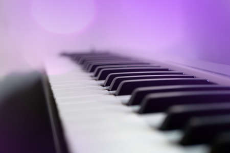 Close-up of musical keyboard synthesizer in violet light. Piano board, USB keyboard, music background. Focus on the middle ground. Zdjęcie Seryjne