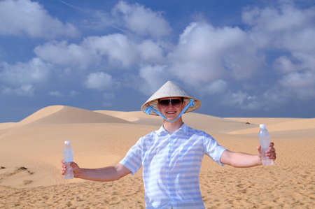Happy Man with two bottles water in the Mui Ne sand Dunes near Phan Thiet, Vietnam. Stock Photo - 12467813