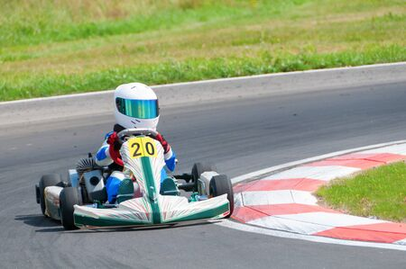 trajectory: Concentrated Young Racer is Driving a Kart And Keeping Trajectory