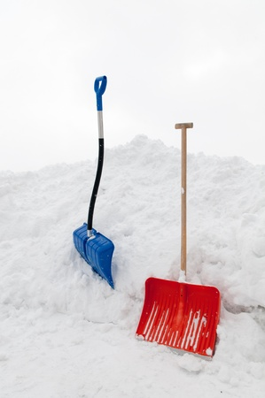 Multicolored snow shovels in snow pile