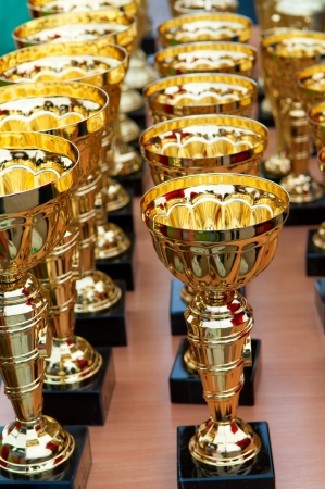 Many shiny gold trophies in a rows Stock Photo - 18849735