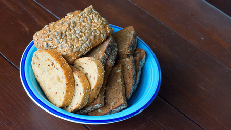 Sliced fresh bread with seeds and sesame on a plate photo
