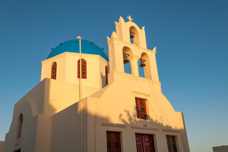 evening church: White Church with Blue Roof in evening light, Santorini, Greece Stock Photo