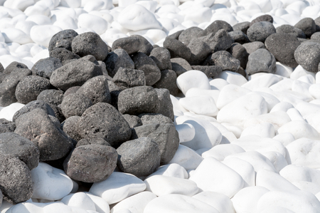 black pebbles: Small white and black pebbles, Santorini Island. Abstract background.