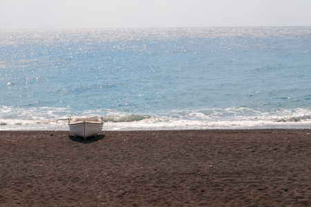 whitw: Boat on Black volcanic beach at Kamari, Santorini, Greece