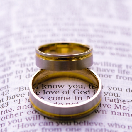 Wedding rings on a Bible with Love of God message Stock Photo