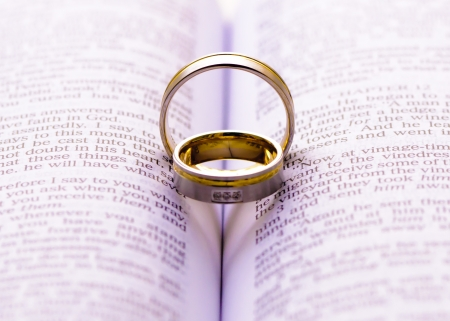 Wedding rings on a Bible with shadow shape heart photo