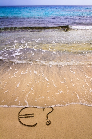 meltdown: Euro sign and question mark in the sand, washed away by sea water, instability concept