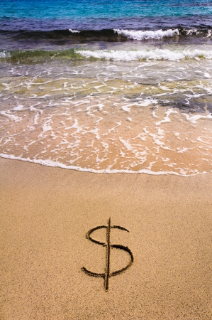 Dollar sign  in the sand being washed away Stock Photo