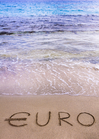instability: Euro word written in the sand on a beach, washed away by sea water, instability concept Stock Photo