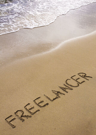 Word FREELANCER written in sand, on a beautiful beach photo