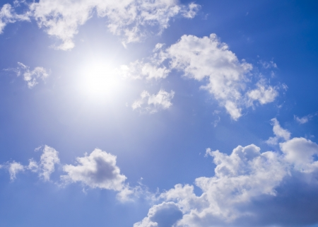 Sun against bright blue sky and white clouds